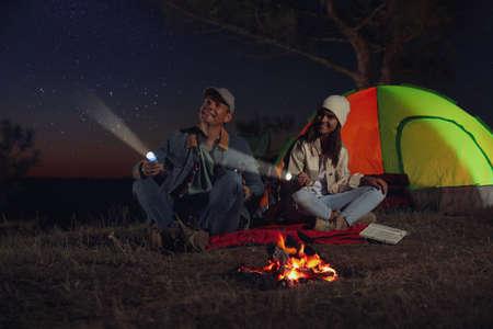 Couple with flashlights near bonfire at night. Camping season Foto de archivo