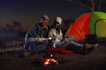 Couple with flashlight near bonfire at night. Camping season