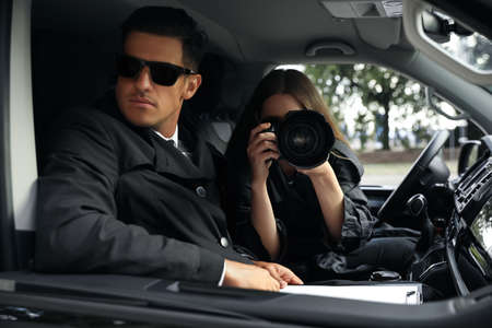 Private detectives with modern camera spying from car