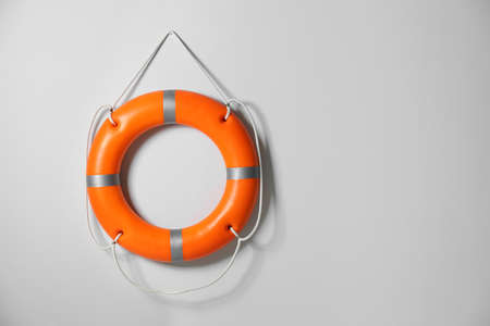 Orange lifebuoy on light background. Space for text