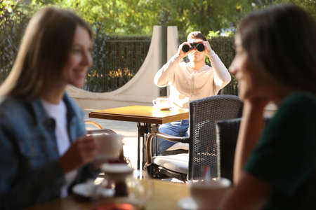 Jealous man spying on ex girlfriend in outdoor cafe