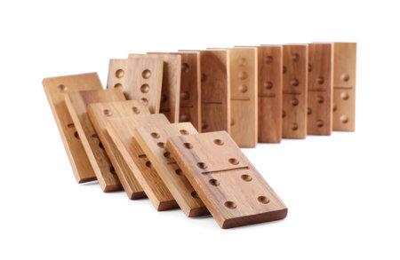 Wooden domino tiles falling on white background