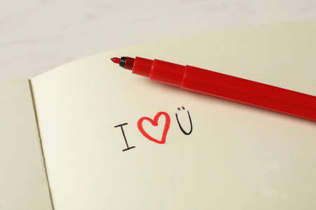 Notebook with text I Love You and red marker on white table, closeup