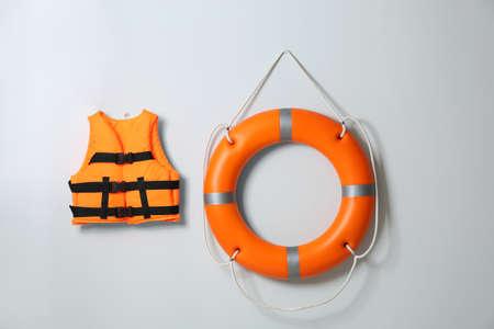 Orange life jacket and lifebuoy on light background. Rescue equipment
