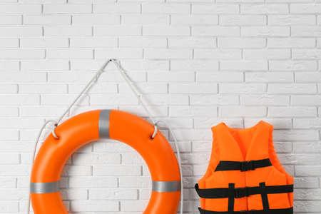 Orange life jacket and lifebuoy on white brick wall. Rescue equipment