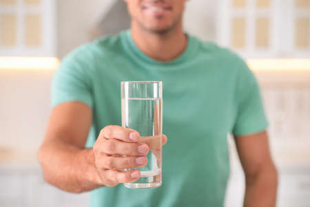 Man holding glass of pure water indoors, closeup