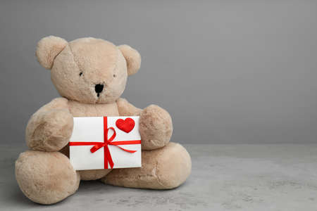 Cute teddy bear with envelope on light grey stone table, space for text. Valentine's day celebration