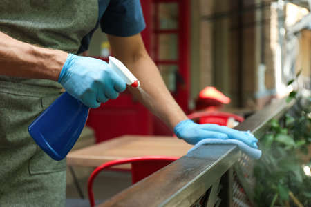 Worker in gloves disinfecting handrail outdoors, closeup