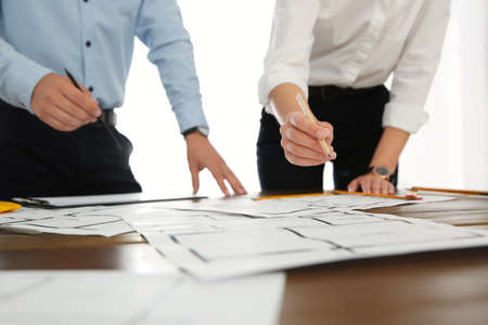 People working with construction drawings at table, closeup