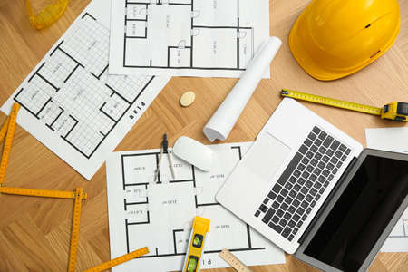 Construction drawings, laptop and tools on wooden table, flat lay