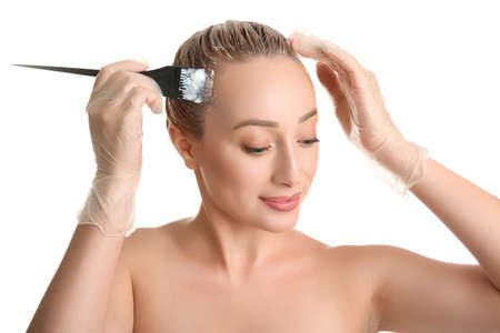 Young woman applying dye on hairs against white background Banque d'images