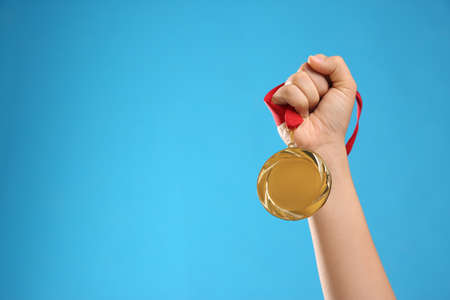 Woman holding gold medal on light blue background, closeup. Space for text