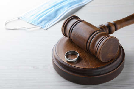 Gavel, wedding ring and protective mask on white wooden table. Divorce during quarantine
