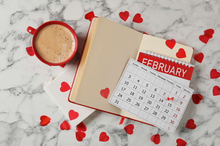 Calendar with marked Valentine's Day, notebooks and cup of coffee on white marble table, flat lay