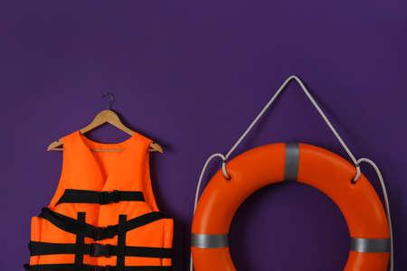 Orange life jacket and lifebuoy on violet background. Rescue equipment Banque d'images