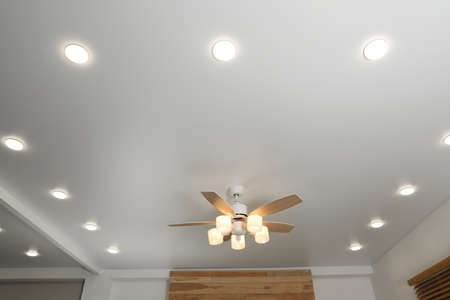 Modern ceiling fan with lamps indoors, below view Фото со стока