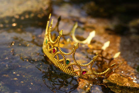 Beautiful golden crown near river, closeup. Fantasy item
