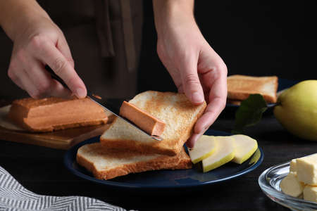 Woman making sandwich with quince paste at table, closeup Stock Photo