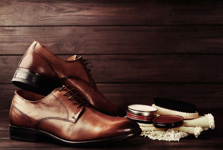 Shoe care accessories and footwear on wooden background