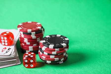 Poker chips, cards and dices on green background, space for text
