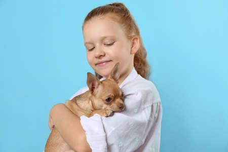 Cute little child with her Chihuahua dog on light blue background. Adorable pet