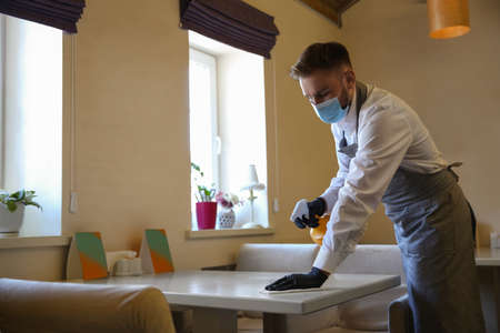 Waiter cleaning table with rag and detergent in restaurant. Surface treatment during coronavirus quarantine Foto de archivo