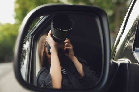 Private detective with camera spying from auto, view through car side mirror Imagens