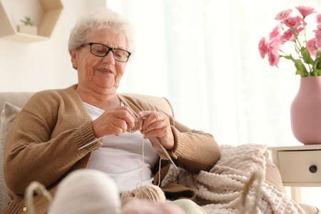 Elderly woman knitting at home. Creative hobby