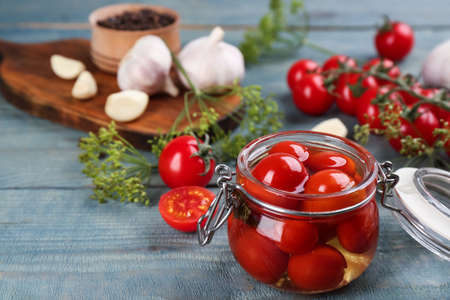 Glass jar of pickled cherry tomatoes on light blue wooden table. Space for text