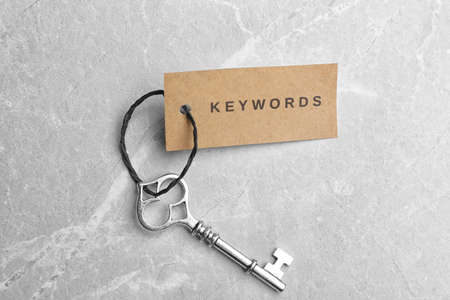 Vintage key and tag wIth word KEYWORDS on light grey table, top view