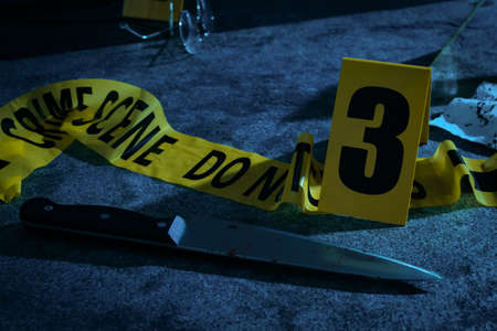 Yellow tape, crime scene marker and bloody knife on grey stone table at night