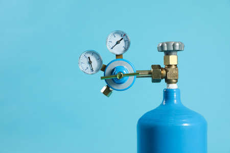 Medical oxygen tank on light blue background. Space for text