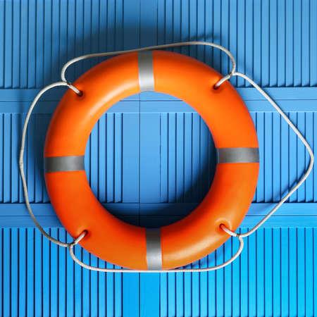 Orange lifebuoy on blue wooden background. Rescue equipment