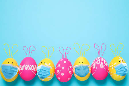 COVID-19 pandemic. Colorful Easter eggs with cute bunny ears in protective masks and space for text on light blue background, flat lay