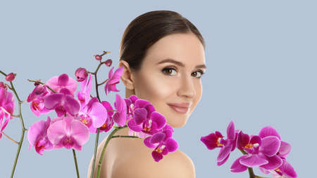 Beautiful young woman and orchid flowers on light background. Spa portrait