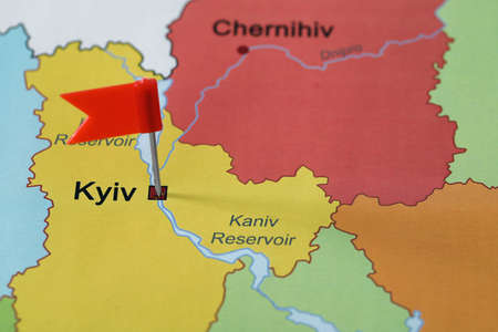 Map of Ukraine with red flag push pin placed on Kyiv, closeup