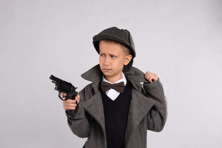 Cute little detective with revolver on grey background