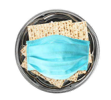 pandemic. Passover matzos and protective face mask on white background, top view