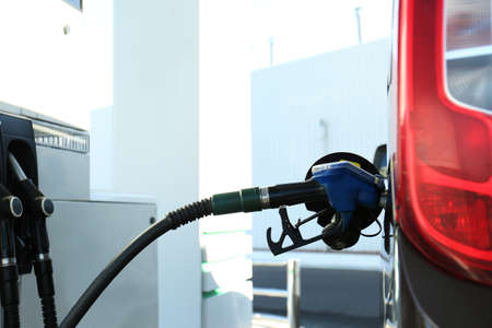 Modern car refilling with fuel at gas station