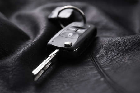 Modern car flip key with trinket on black leather, closeup