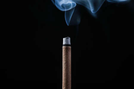 Incense stick smoldering on black background, closeup