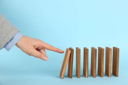 Woman causing chain reaction by pushing domino tile on light blue background, closeup