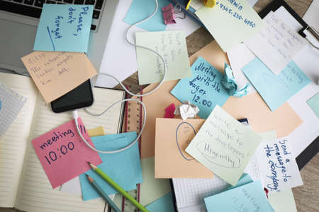 Laptop, notes and office stationery in mess on desk, top view. Overwhelmed with work