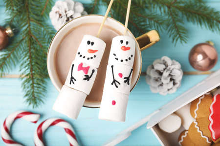 Flat lay composition with funny snowmen made of marshmallows in cup of hot drink on light blue wooden table