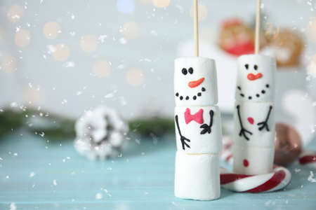 Funny snowmen made of marshmallows on light blue wooden table, closeup. Space for text