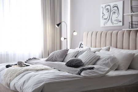 Cozy bedroom interior with cushions and striped blanket