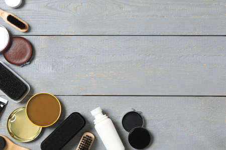 Flat lay composition with shoe care accessories on wooden background, space for text