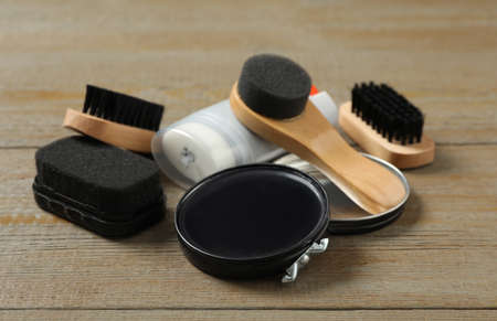 Composition with shoe care accessories on wooden background, closeup
