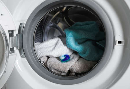 Laundry detergent capsule and towels in washing machine drum, closeup view