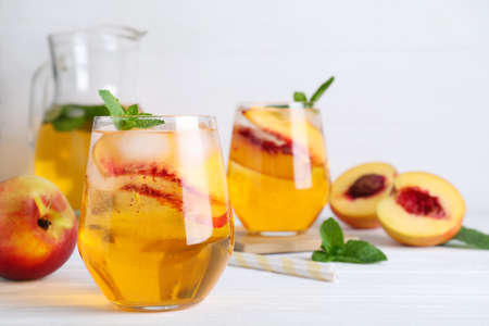 Delicious peach lemonade made with soda water and ingredients on white wooden table. Space for text